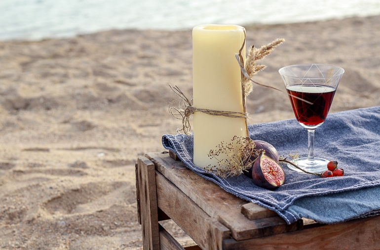 Candle with fruit and glass of red liquid on crate with sand and water in background
