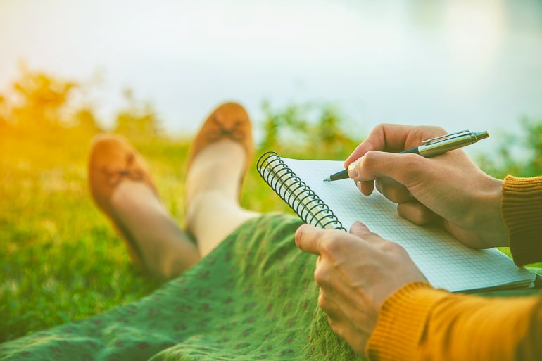 Woman sitting on grass with notebook and pen in hand