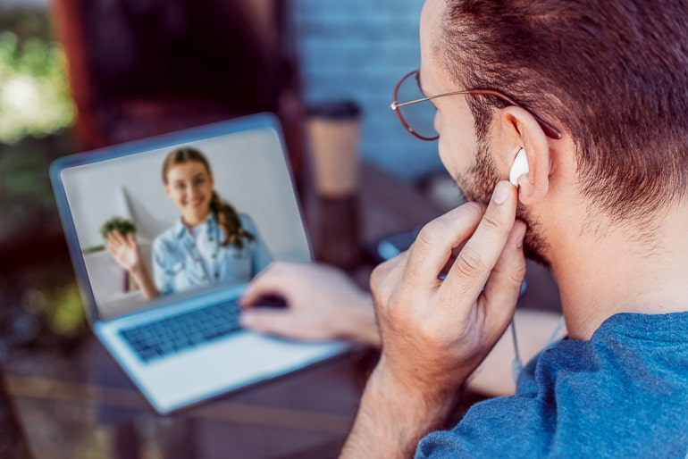 Man with headphones videochatting with woman on laptop long distance