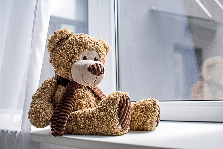 Brown teddy bear with scarf sitting on white window sill