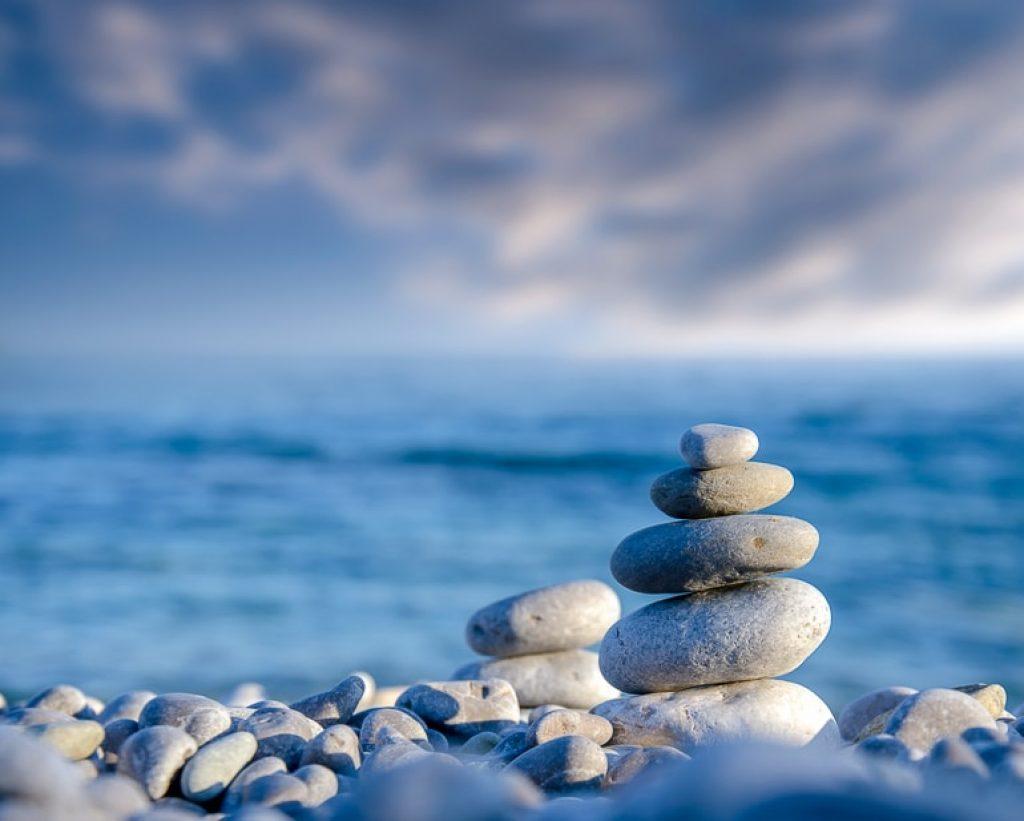 stones balancing on shoreline with sea behind