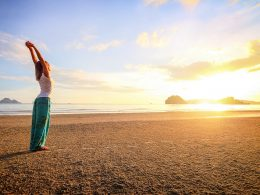 woman standing on sandy beach with sunset mantras for anxiety