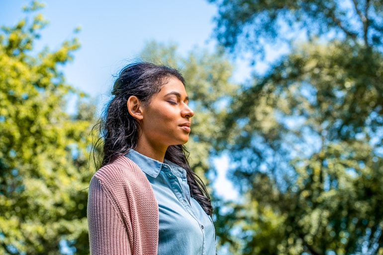 woman breathing outside with eyes closed mantras for anxiety