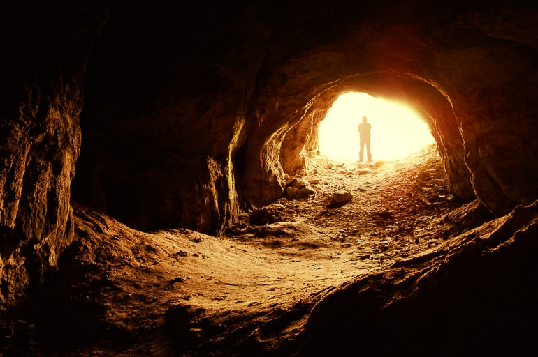 person looking into dark cave opening