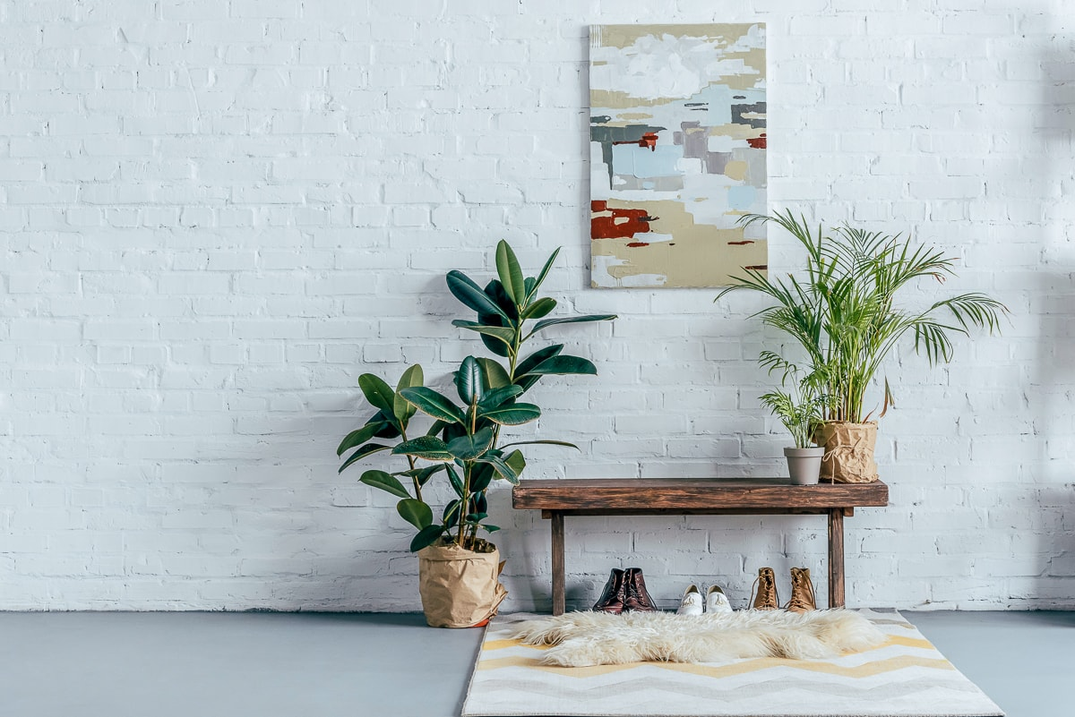 Wood bench with plants and shoes in front of white brick wall with photo minimalist design tips