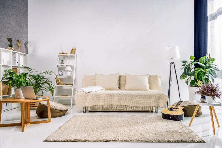 Living room in natural colors with plants and white wall