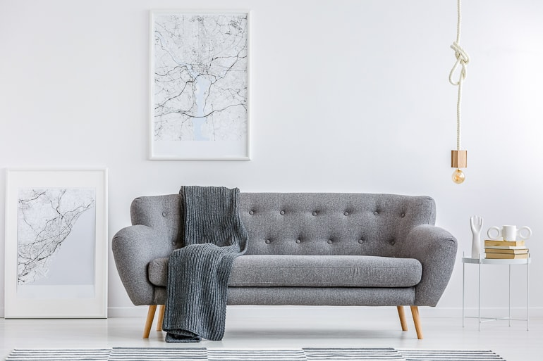 Grey couch with grey blanket in front of white wall with black and white pictures