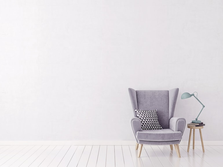 Comfy grey chair with pillow next to white wall on white wood floor
