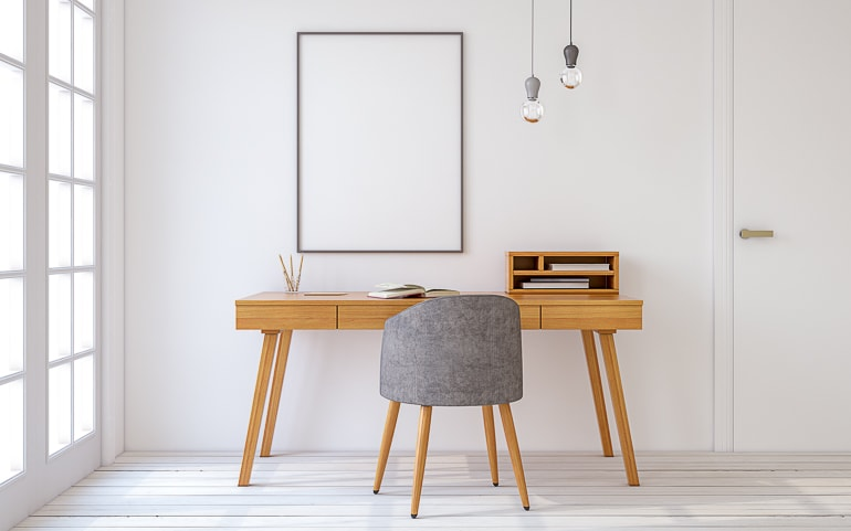 Wood desk and grey chair in room with white floor and white wall minimalism