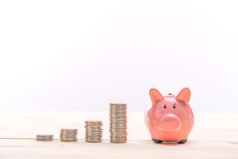 coins and pink piggy bank for money saving tips