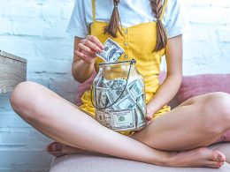 Woman sitting and holding jar of money in lap for money saving challenges