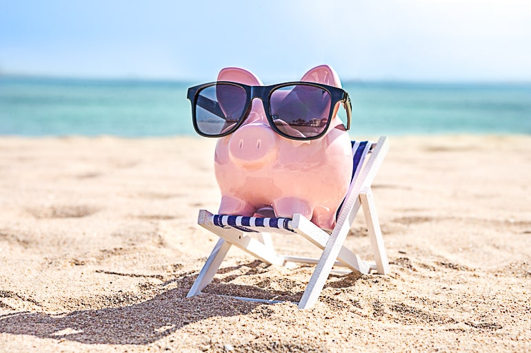 Piggy bank on beach chair with dark sunglasses for saving money article
