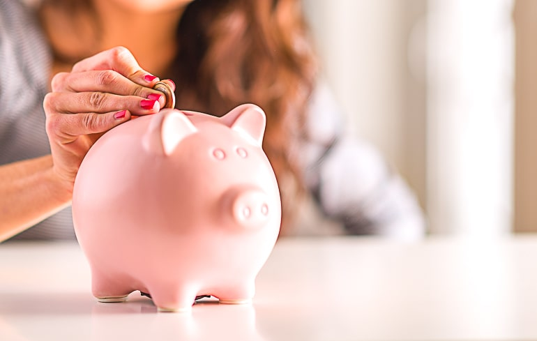 Woman putting coin in pink piggy bank