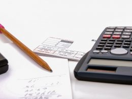 Calculator pencil and paper on white desk monthly expense tracker