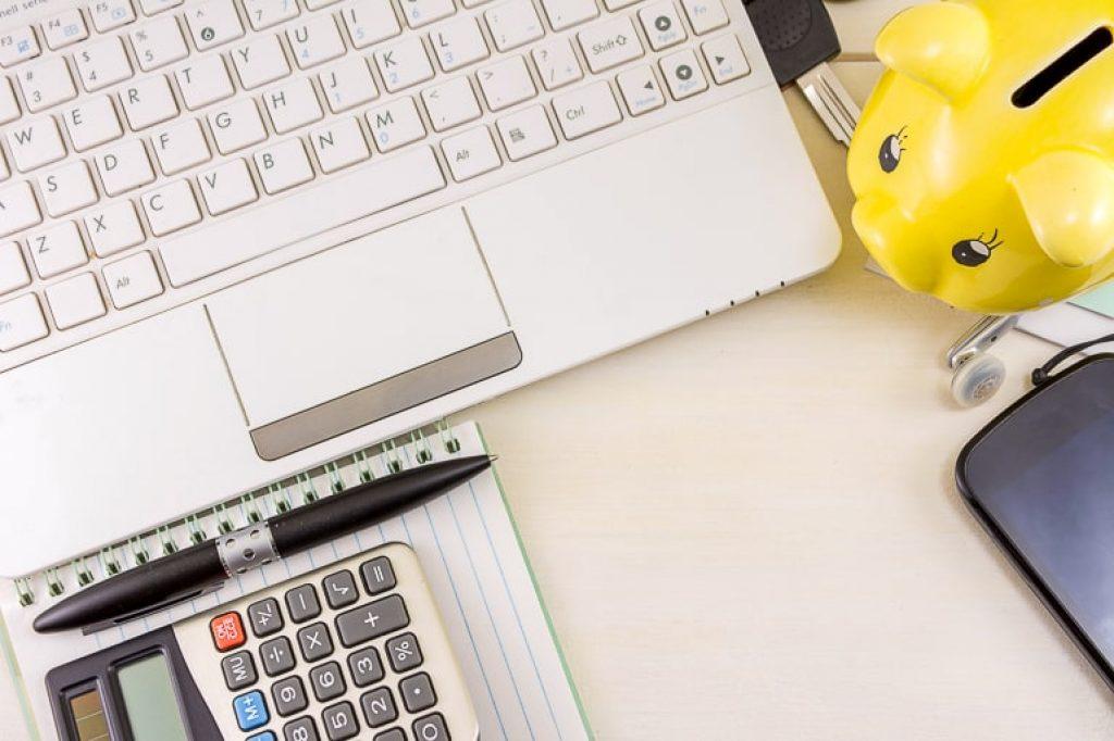 Computer piggy bank calculator and notebook on desk