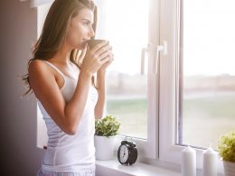 Woman holding mug and looking out a window morning routine checklist for adults