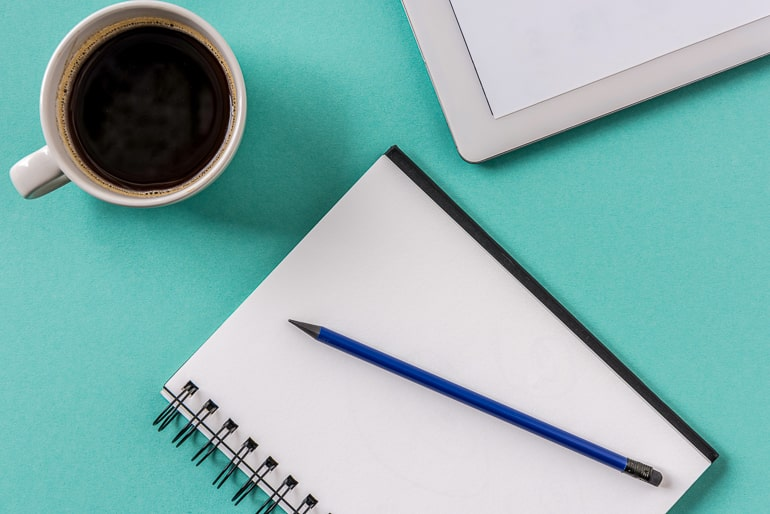 open journal with pen and coffee mug beside on blue table