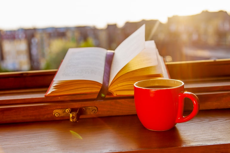 open book with orange mug beside on windowsill