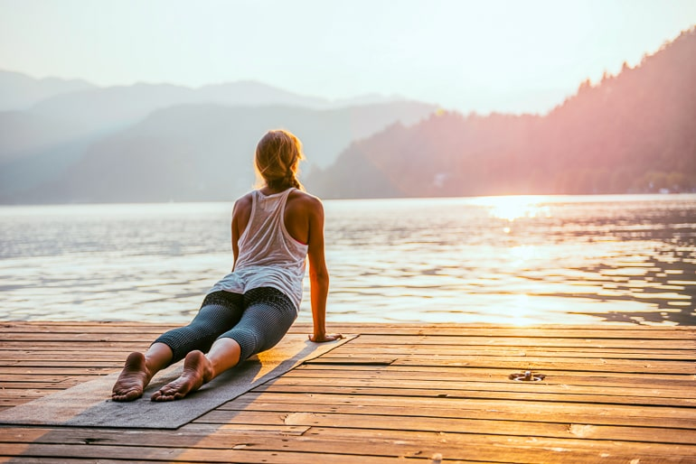 woman doing yoga pose on wooden dock with sun in front new years resolution ideas