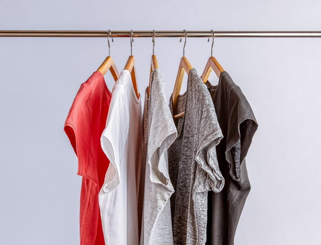 five shirts on hangers on metal rod not buying new clothes for a year