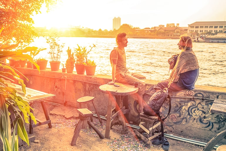 Man and woman sitting on wall next to river talking