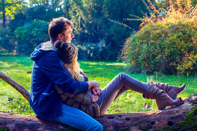 Man and woman sitting embraced on fallen tree with green grass in background