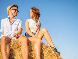 Man with hat and woman sitting on ball of hay looking at each other relationship insecurity