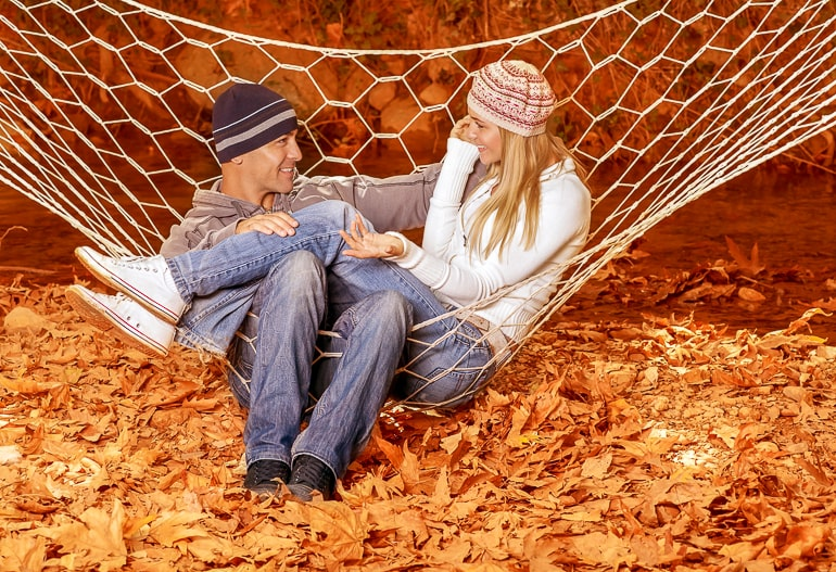 Man and woman sitting in white hammock looking at each other with fall leaves on ground