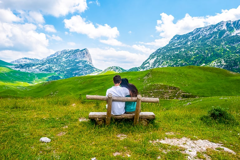 Couple sitting on wood bench with green grass and tall mountains in background self care