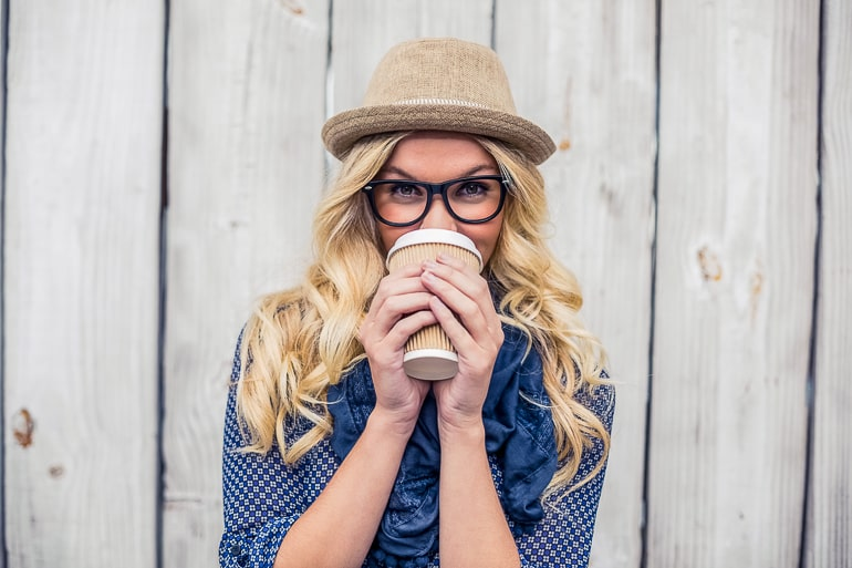 Blonde woman with hat gasses holding a coffee cup in her hand