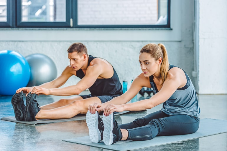 Man and woman in workout clothes sitting on mat and stretching
