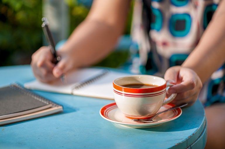Person holding coffee mug and writing in journal on blue table