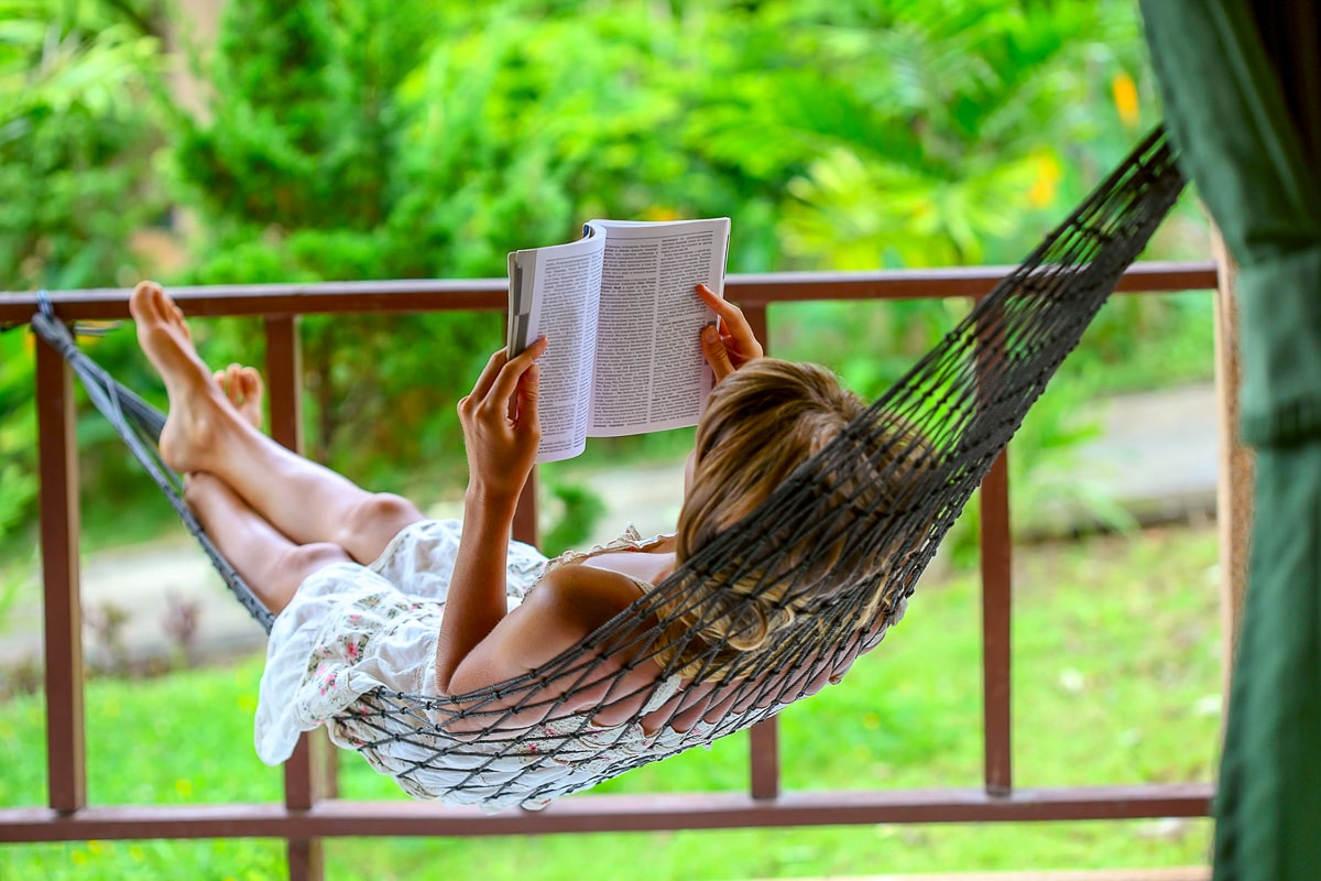 Woman in hammock reading a book with greenery in background self care tips