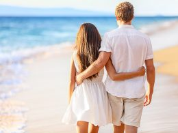 Couple walking on the beach with arms around each other separation anxiety in a relationship
