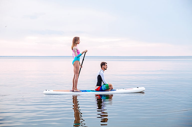 Man sitting on Stand Up Paddleboard with woman standing behind him on lake