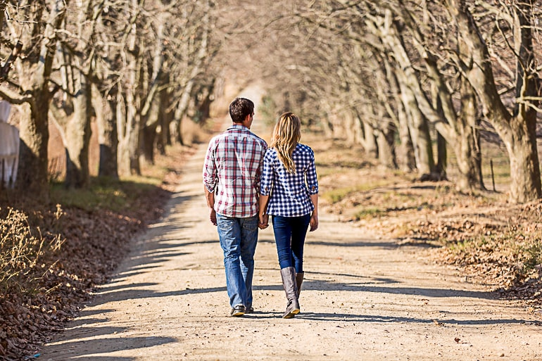 Man and woman in relationship holding hands walking on path lined with trees
