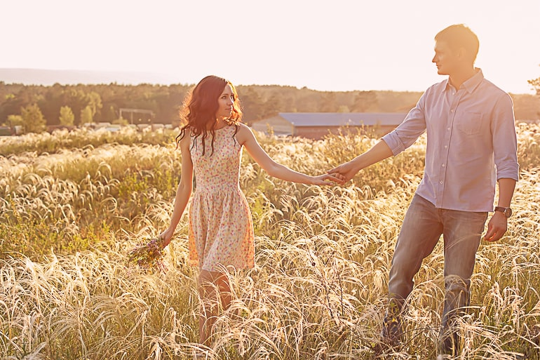 Couple walking in field holding hands and looking at each other separation anxiety