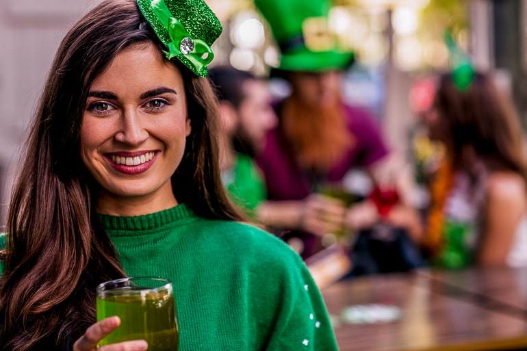 woman wearing green and green hat with st patricks day party behind