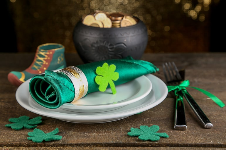 green rolled napkin in white plate with pot of gold behind on wooden table