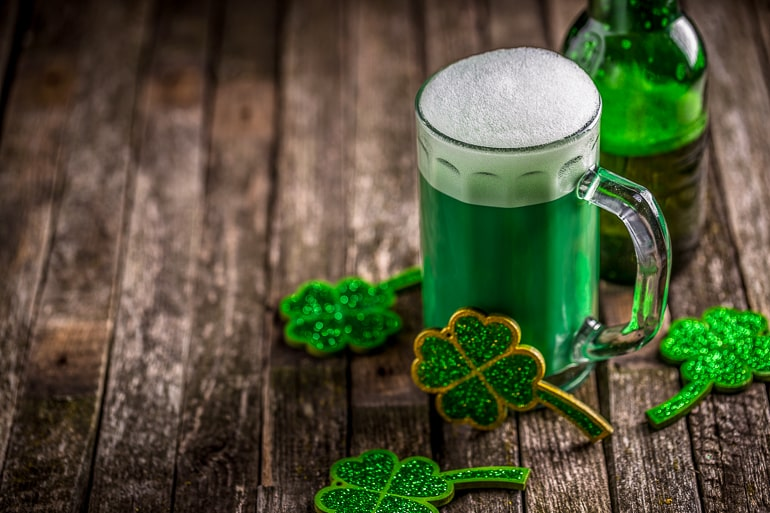 mug of green beer on wooden table for st patricks day