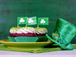 dark cupcakes with icing and green irish flags in top beside green hat st patricks day party