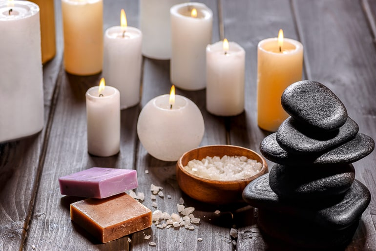 Candles soaps and stones standing on dark wood background stressful day