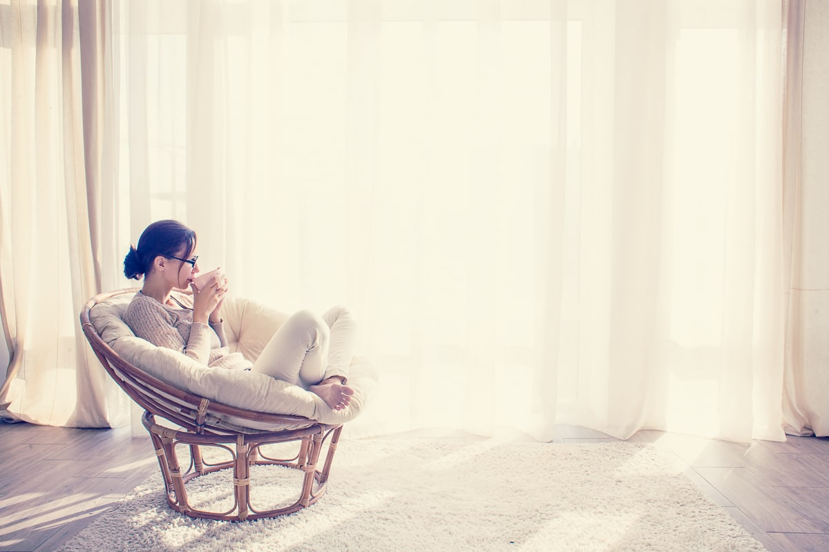 Woman sitting in comfortable chair and holding a mug in front of white curtains