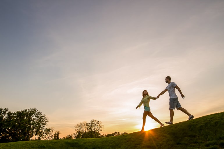 Man and woman walking on grass and holding hands with setting sun in background