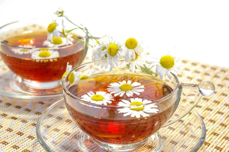 chamomile flowers in clear tea mug on clear plate