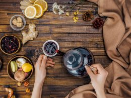 hands pouring tea from pot into mug on wooden table tea flavors