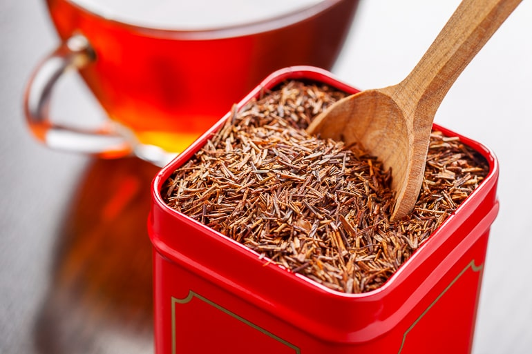 red rooibos tea in red container with wooden spoon tea flavors