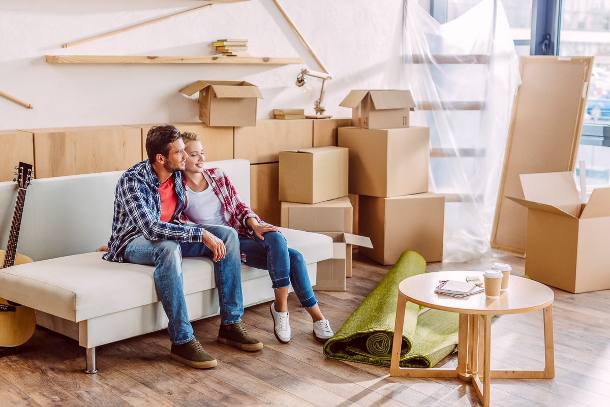 Couple sitting on couch with moving boxes around them things to discuss before moving in together