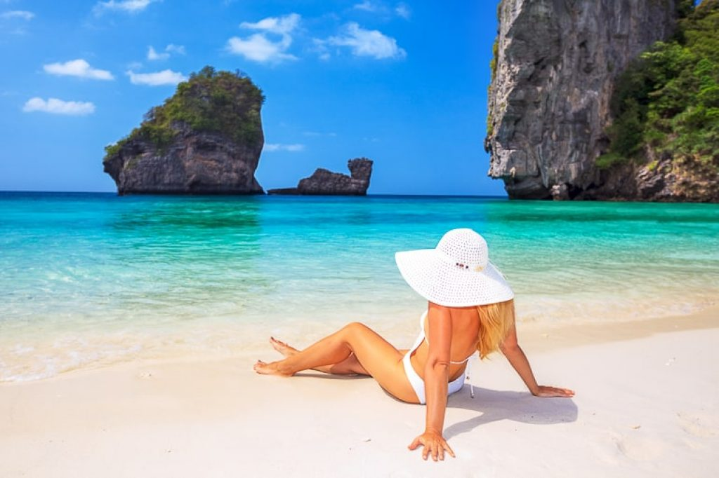 Woman in white bikini with white hat sitting on sandy beach with clear water and cliffs in background