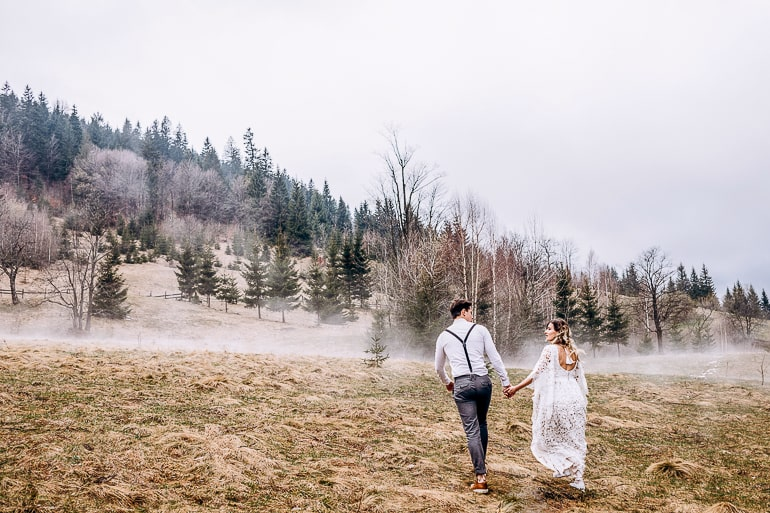 Couple holding hands and walking on grass with trees and fog in background